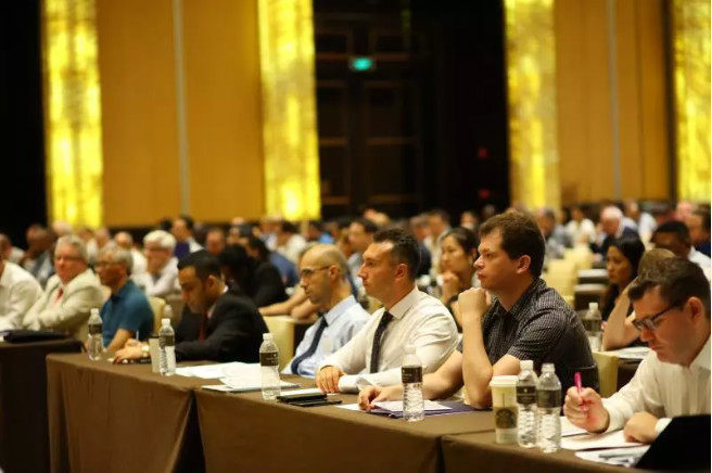 Attendees sit listening at a conference