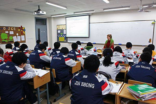 A teacher in front of whiteboard speaks to a class of Chinese students sitting in rows of desks