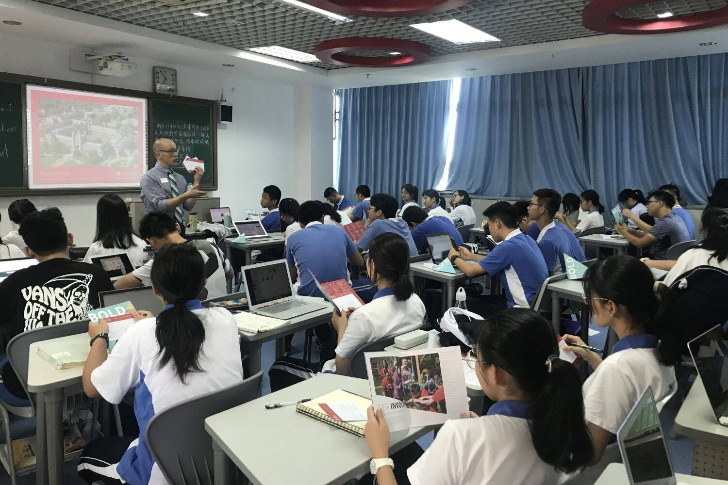 A teacher gives a presentation to a classroom full of Chinese students sitting at desks