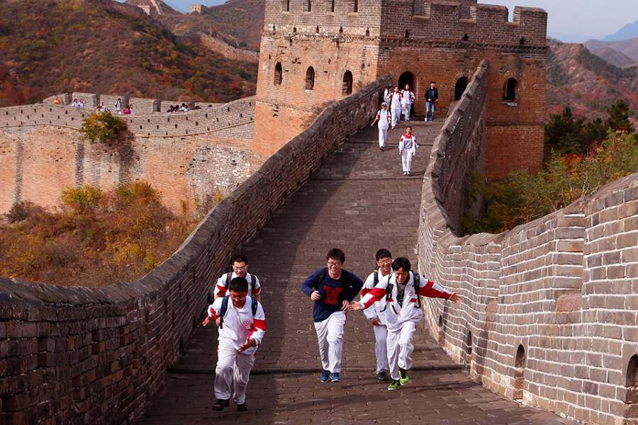 School children run on the Great Wall of China