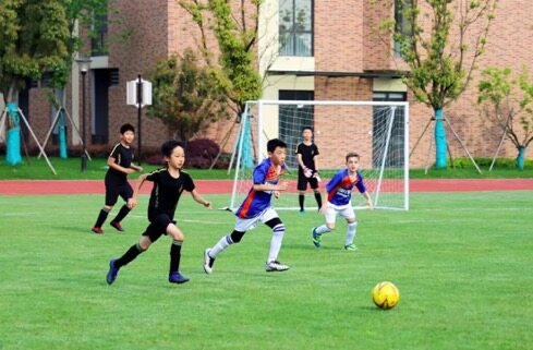 Pupils play football at King's College School Hangzhou