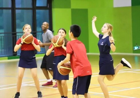 Pupils play basketball at King's College School Hangzhou