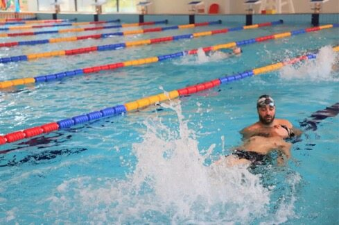 A King's College School Hangzhou pupil receives swimming instruction from a teacher