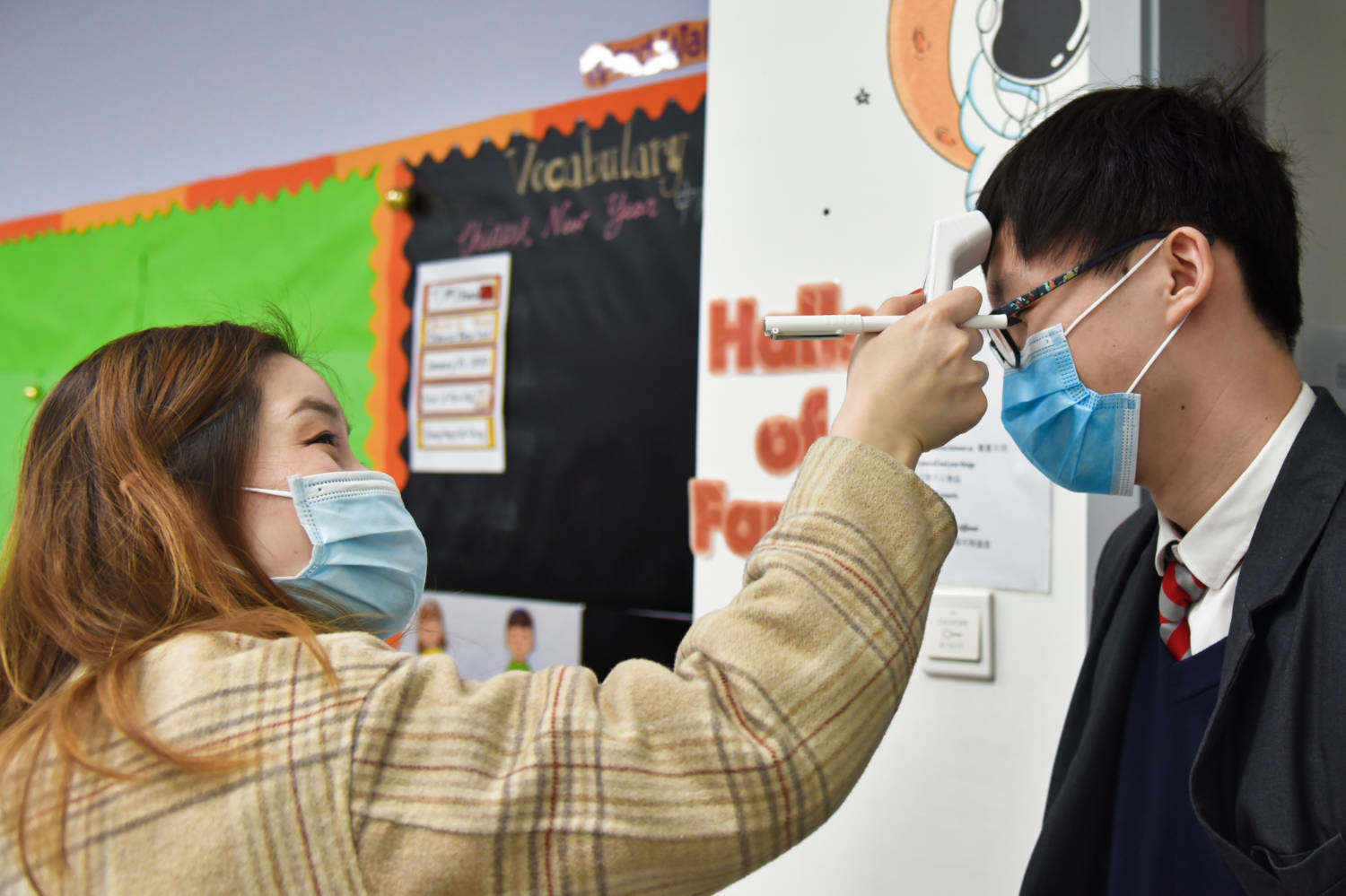 A pupil at Nanwai King's College School Wuxi has his temperature checked