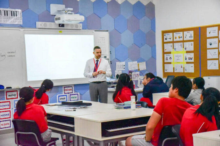 A teacher standing in front of a class of students