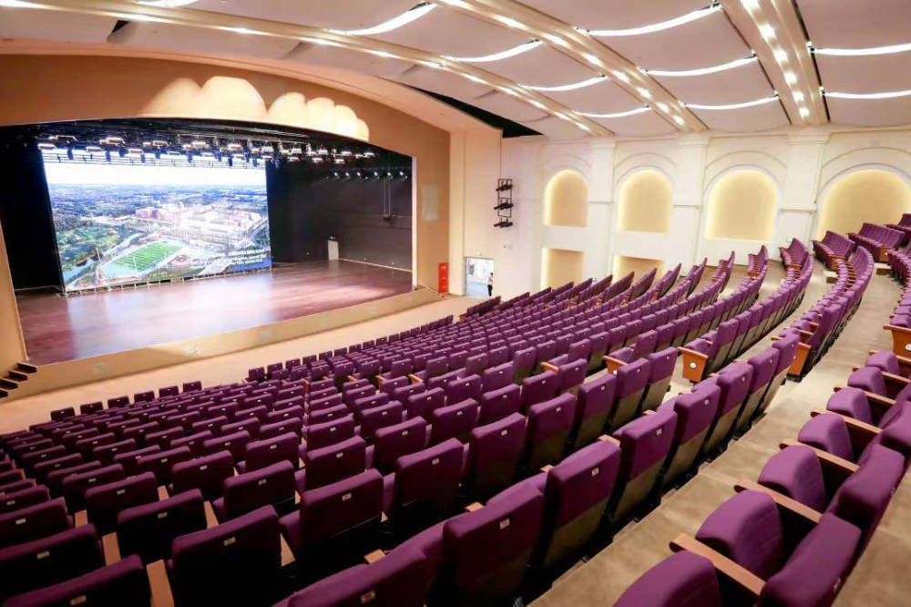 An auditorium with rows of seats and a stage