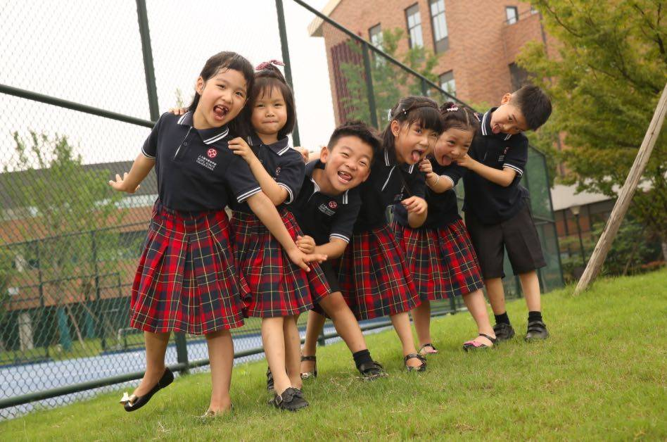 A group of school children smile for the camera