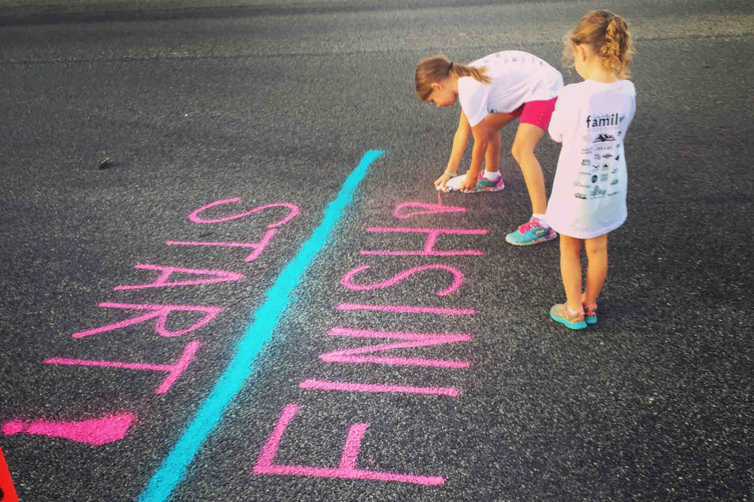 Children stand next to the words start and finish written on the ground in chalk